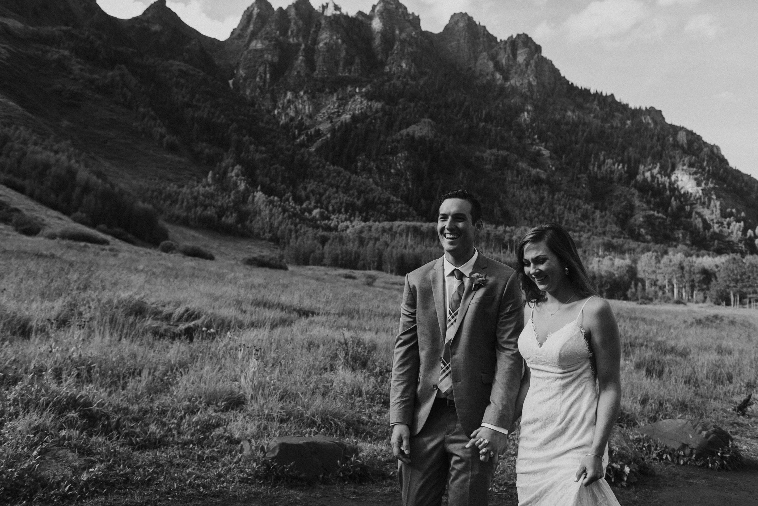 Heather and Darren laughing as they walk the trails at the Maroon Bells on their wedding day.