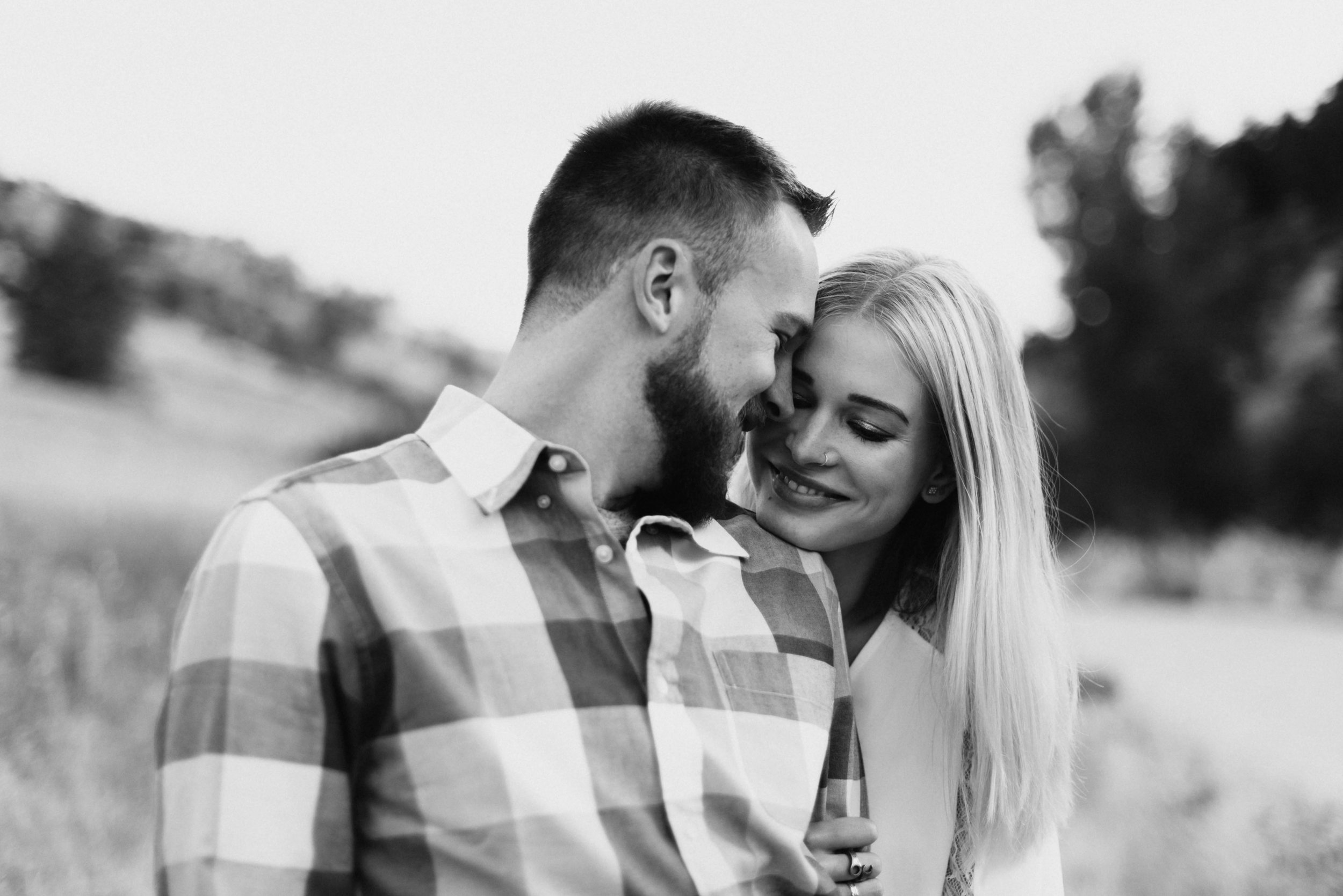 A black and white image of Betsy hugging Connor during their hiking engagement session at Mount Sanitas.