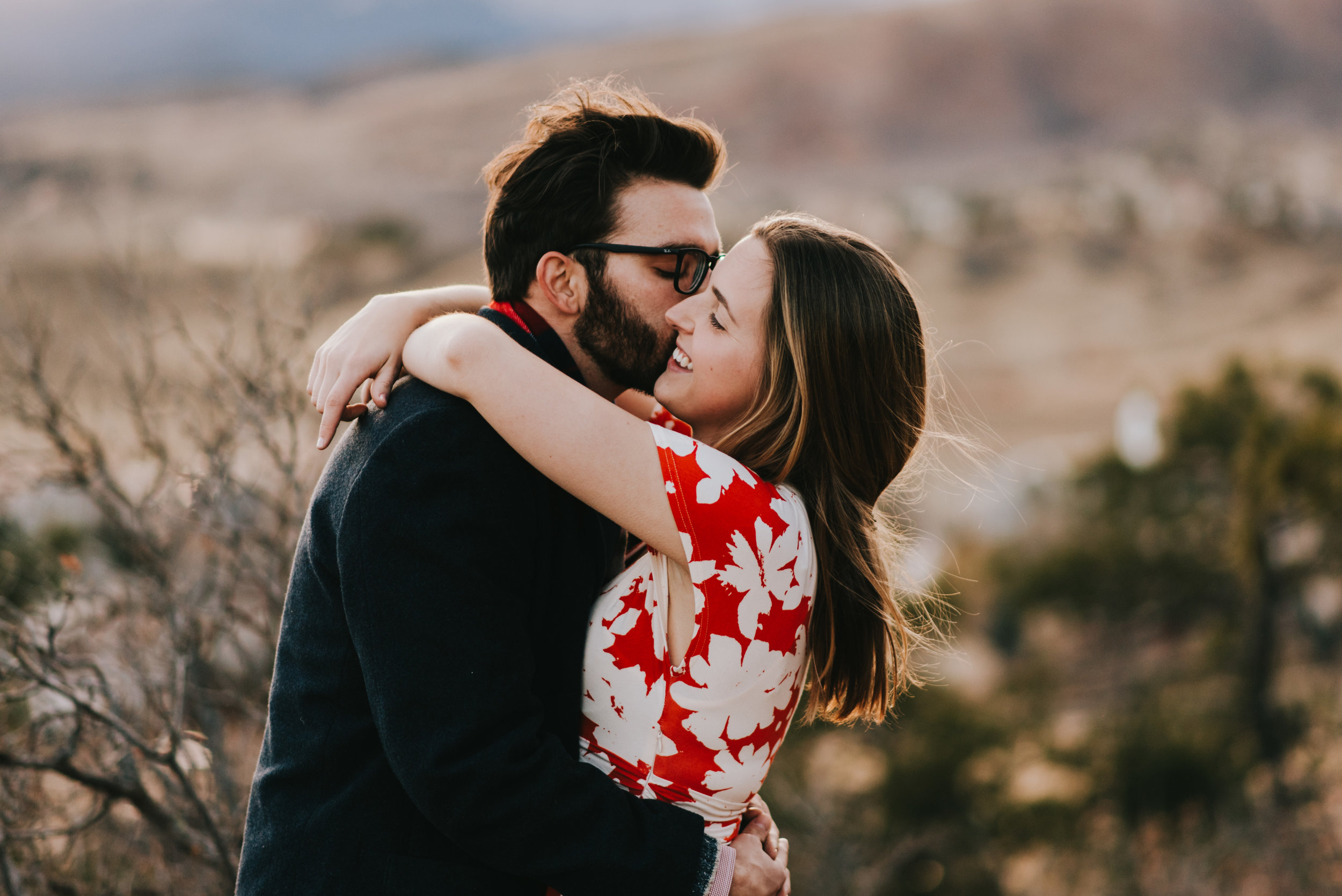 Ted kissing Rachel on the cheek during their Colorado Springs engagement session at Garden of the Gods.
