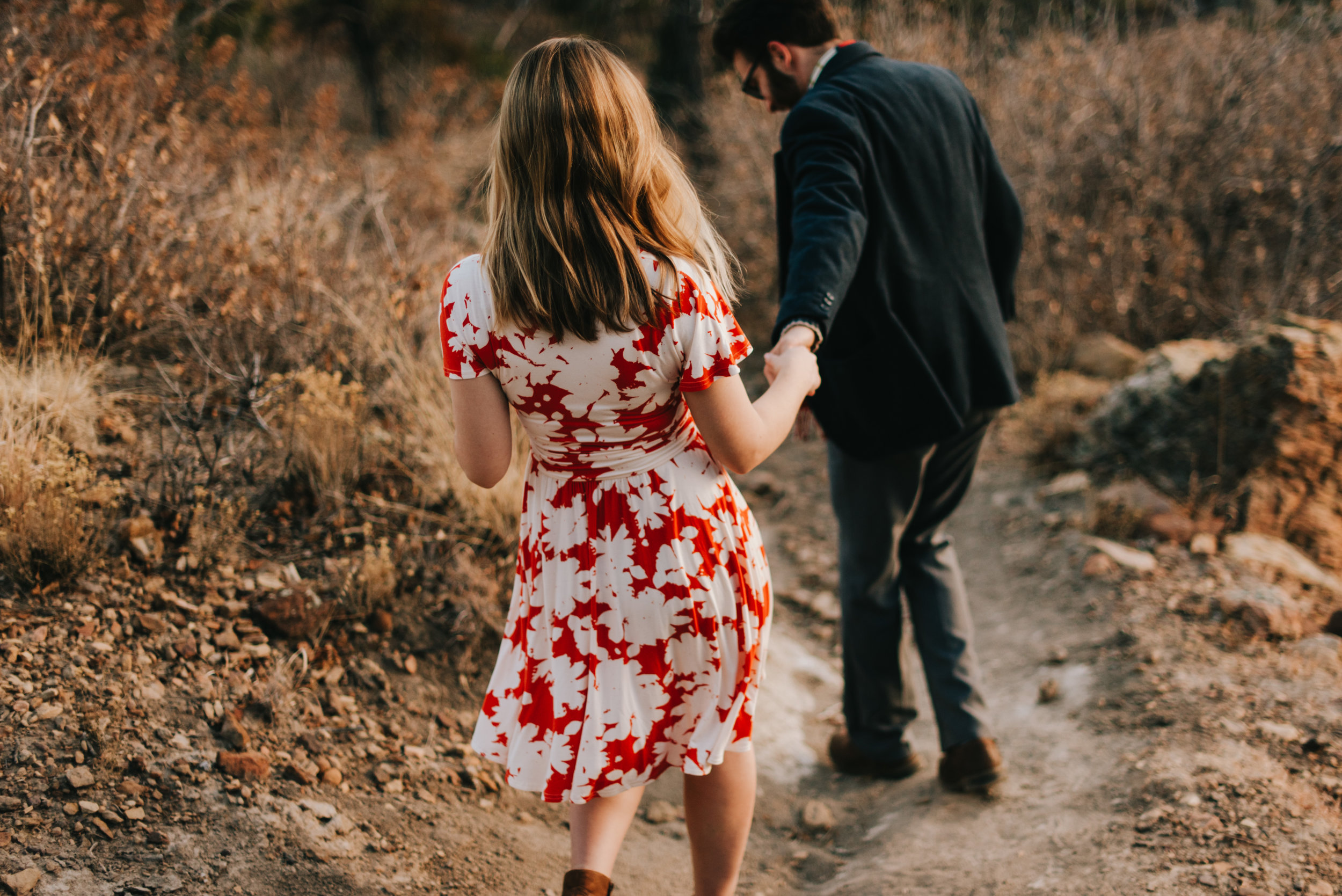 Ted and Rachel walking hand in hand during their engagement session.