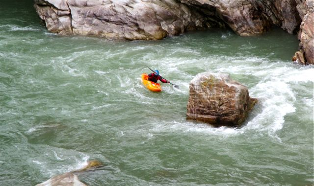 A kayaker breaking out of the current into an eddy