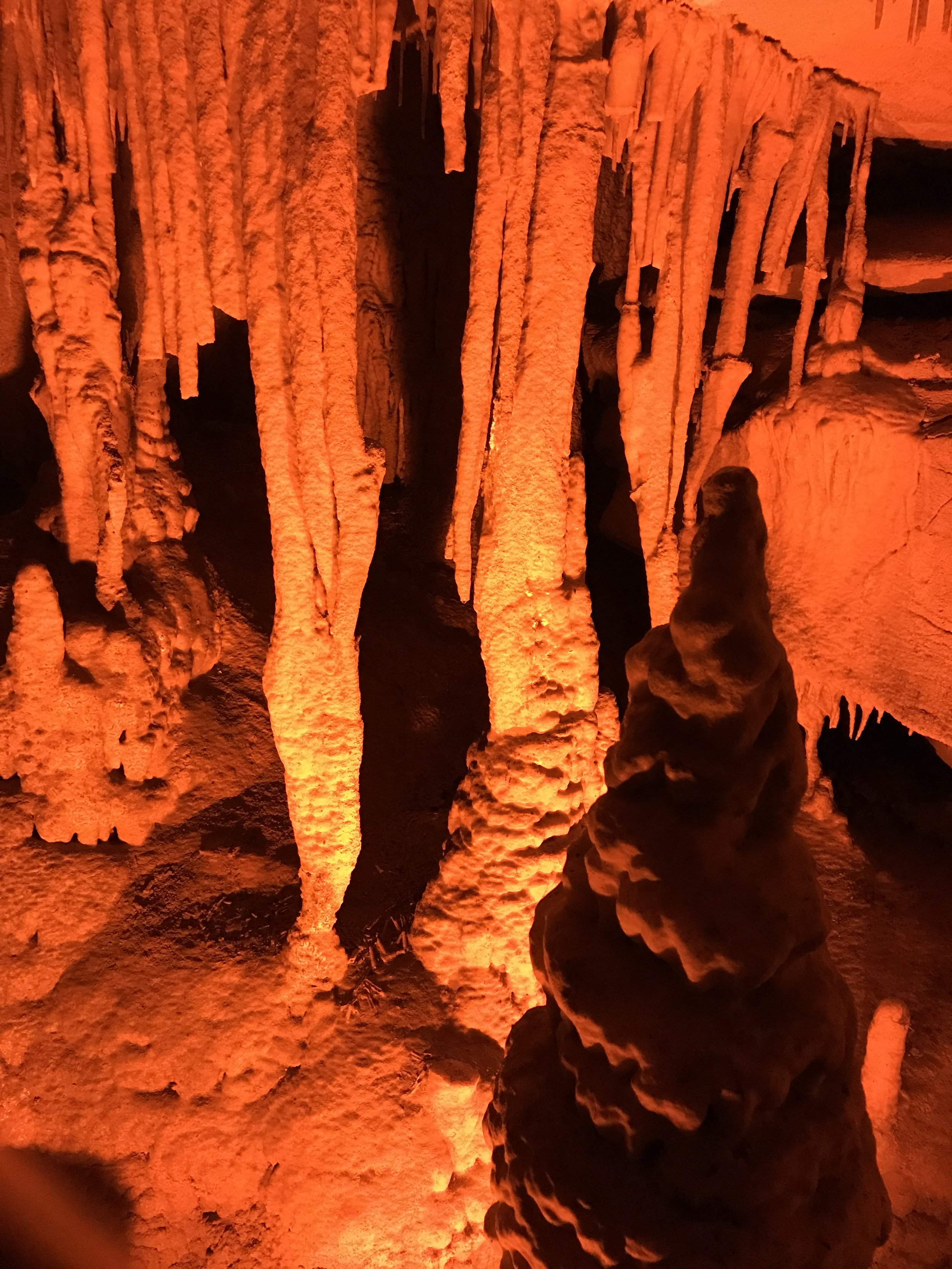 """Here is a view of the stalactites, stalagmites, and columns that we saw at the end of our Domes and Dripstones tour at Mammoth Cave. The only lights in the cave were the occasional orange low lights that lit our way. No flash photography. So amazing the long process that it has taken for these rock formations to """"grow."""" It was also very cool when our tour guide turned off all the lights in the cave. We could see absolutely nothing! How often do we experience zero light like that?"""