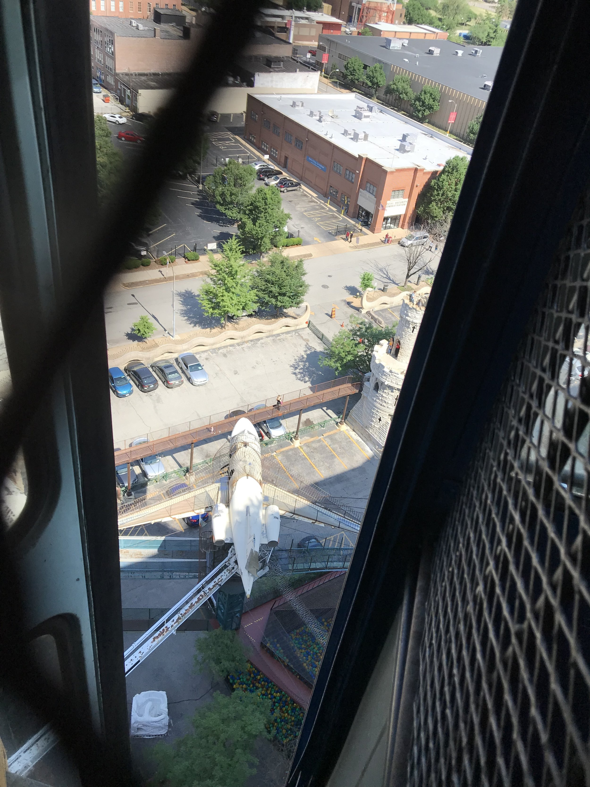 Our view from the door of the school bus that is half-suspended from the 11-story roof at the City Museum, looking out over the old airplane that people can also climb to- via a tunnel.