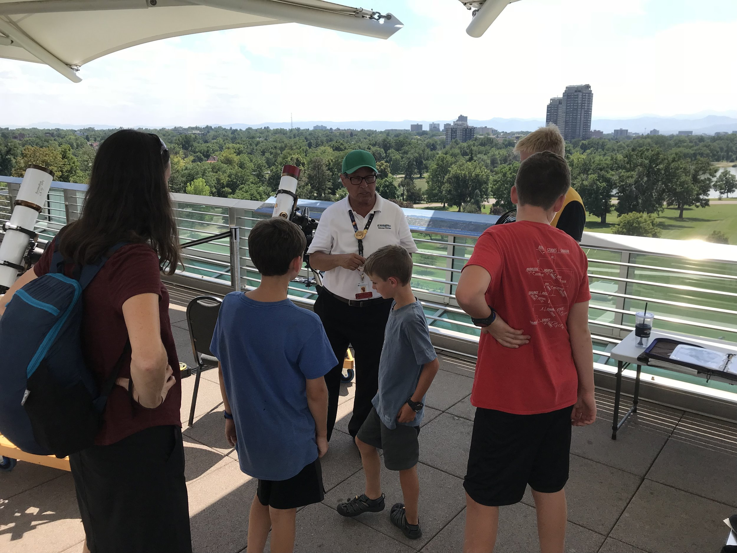 On our way to Boulder (i.e., driving the rental vehicle), we stopped for a couple of hours at the Denver Museum of Nature and Science. In this picture we are on the roof top being guided to look at the sun through some special telescopes.