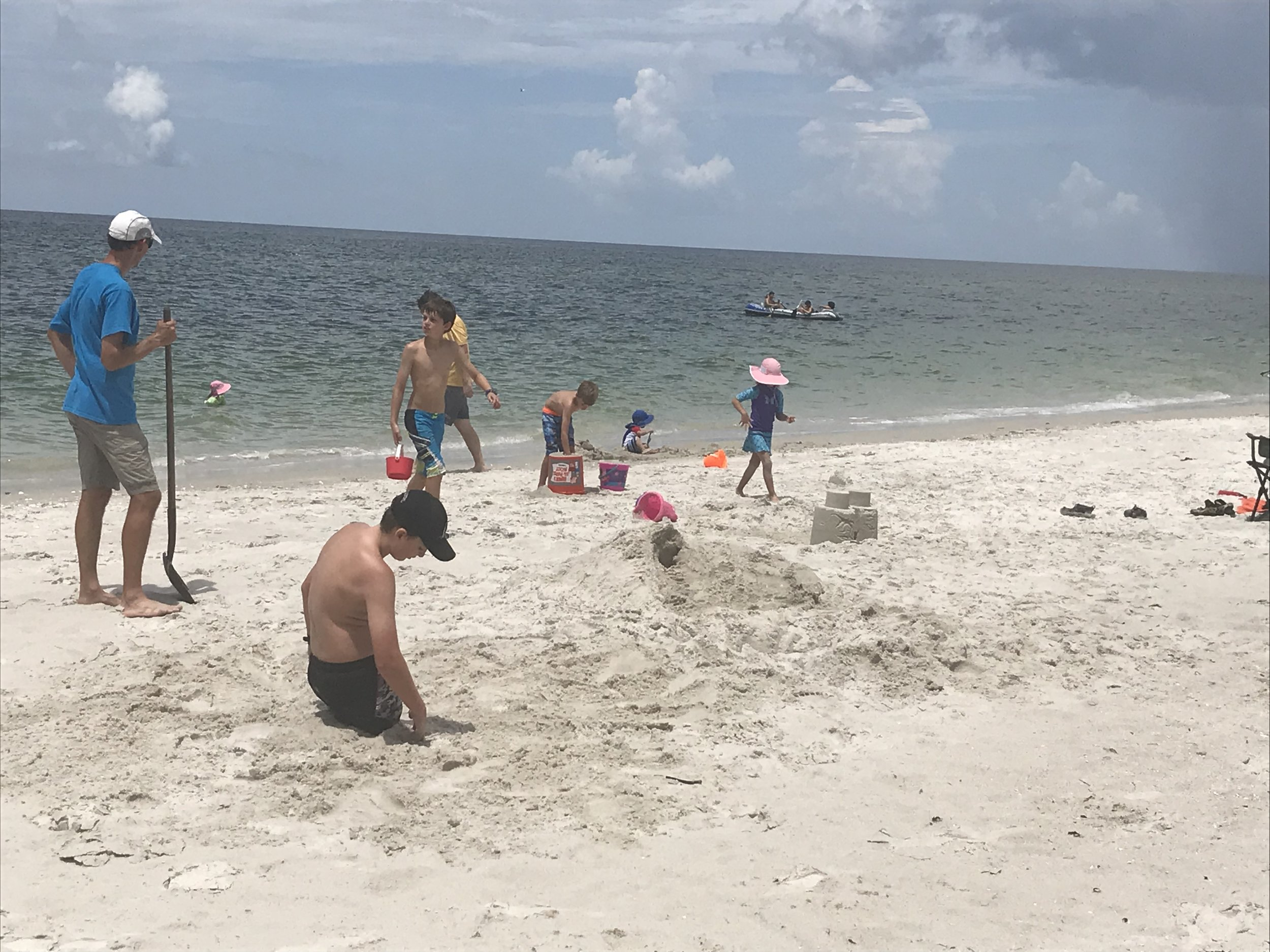 Digging holes, building sand castles, and playing in the warm and calm Gulf coast waters with our new friends, the Floods.
