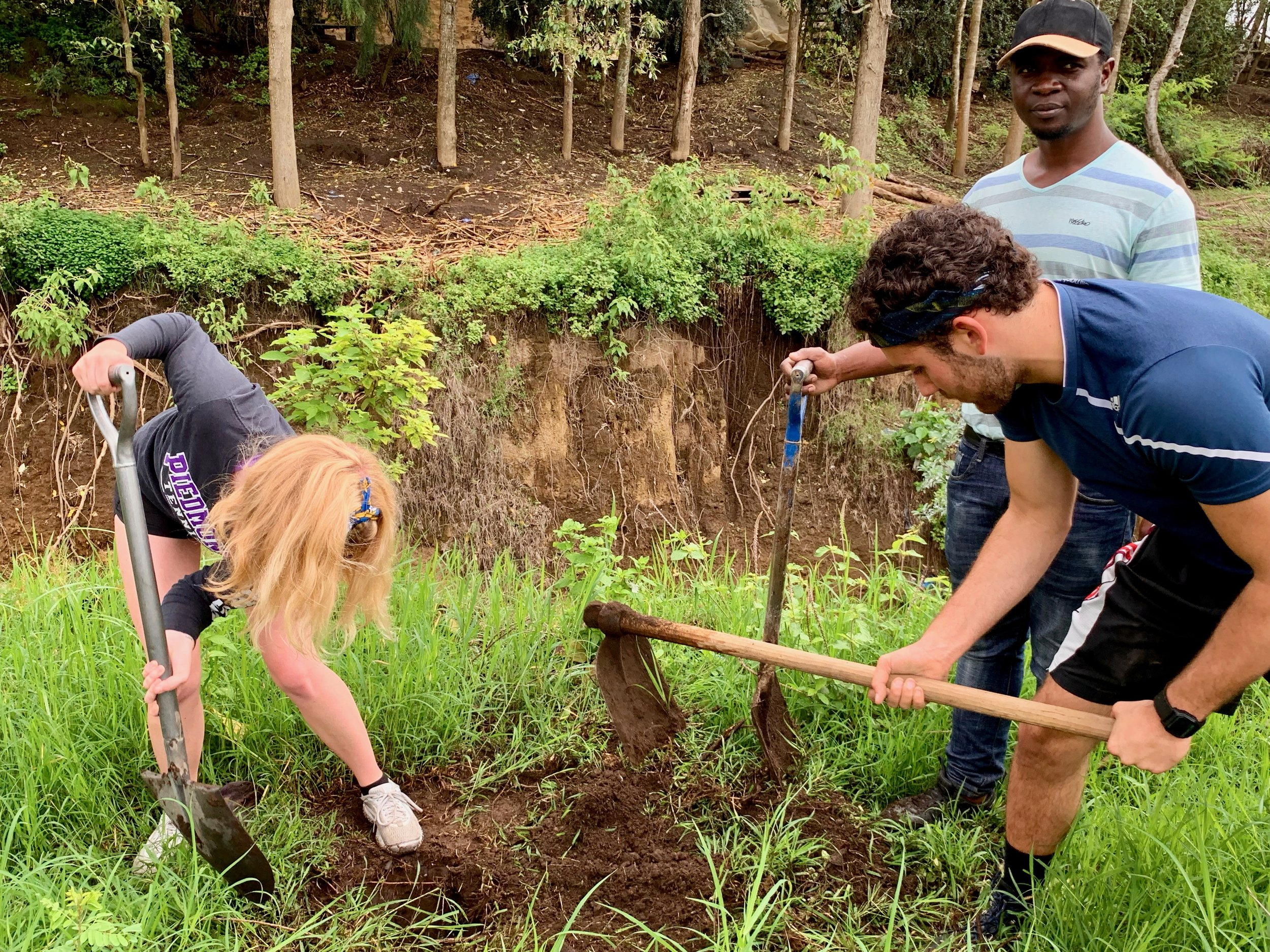The students planting in front of the ravine, which you can see behind them.