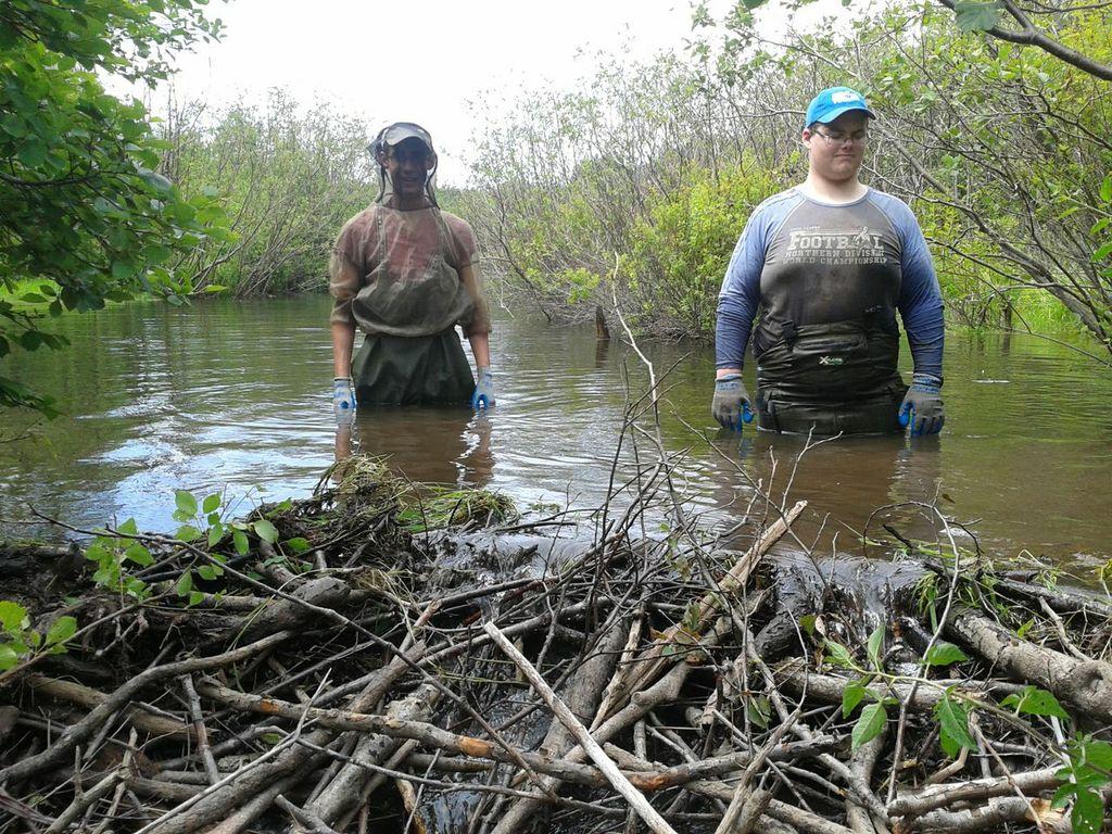 Kyle Lefort (gauche) et Jeremy Camus (droite) derrière un barrage de castor sur le ruisseau Aucoin.