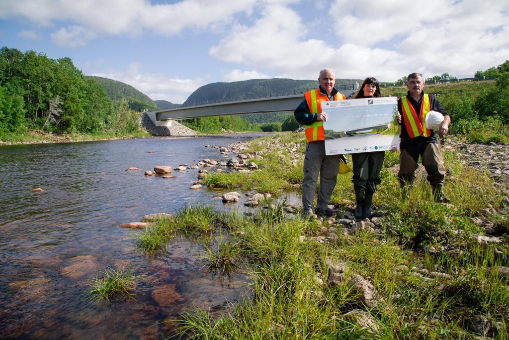 Archie Doucette (Parks Canada), Jillian Baker (CRSA), and Charles MacInnis (project consultant) displaying official project sign at the end of the construction phase.