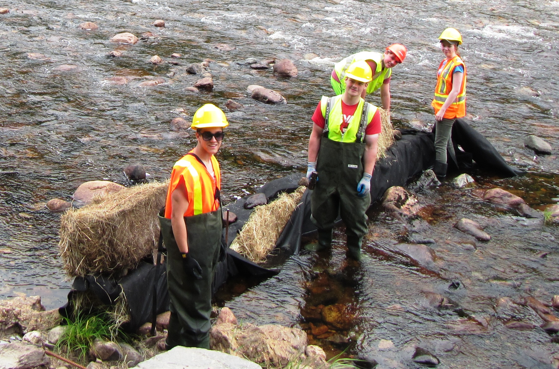 Cheticamp River Salmon Association's student work crew setting up sediment control measures before the start of instream work