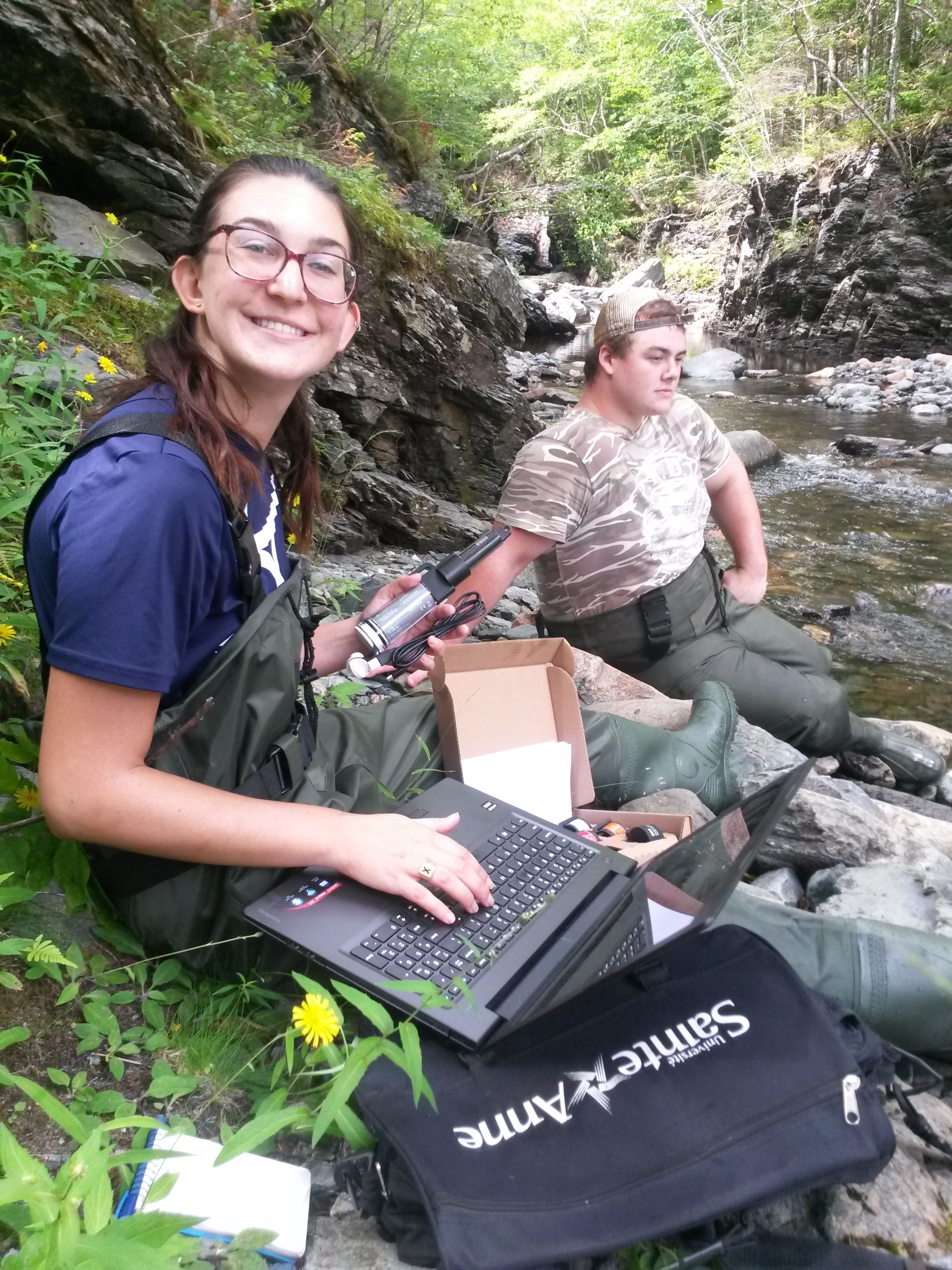 Gabrielle MacLaughlin and Jeremy Camus - summer student with the CRSA - retrieving water temperature data from one of the data loggers installed on the Cheticamp River
