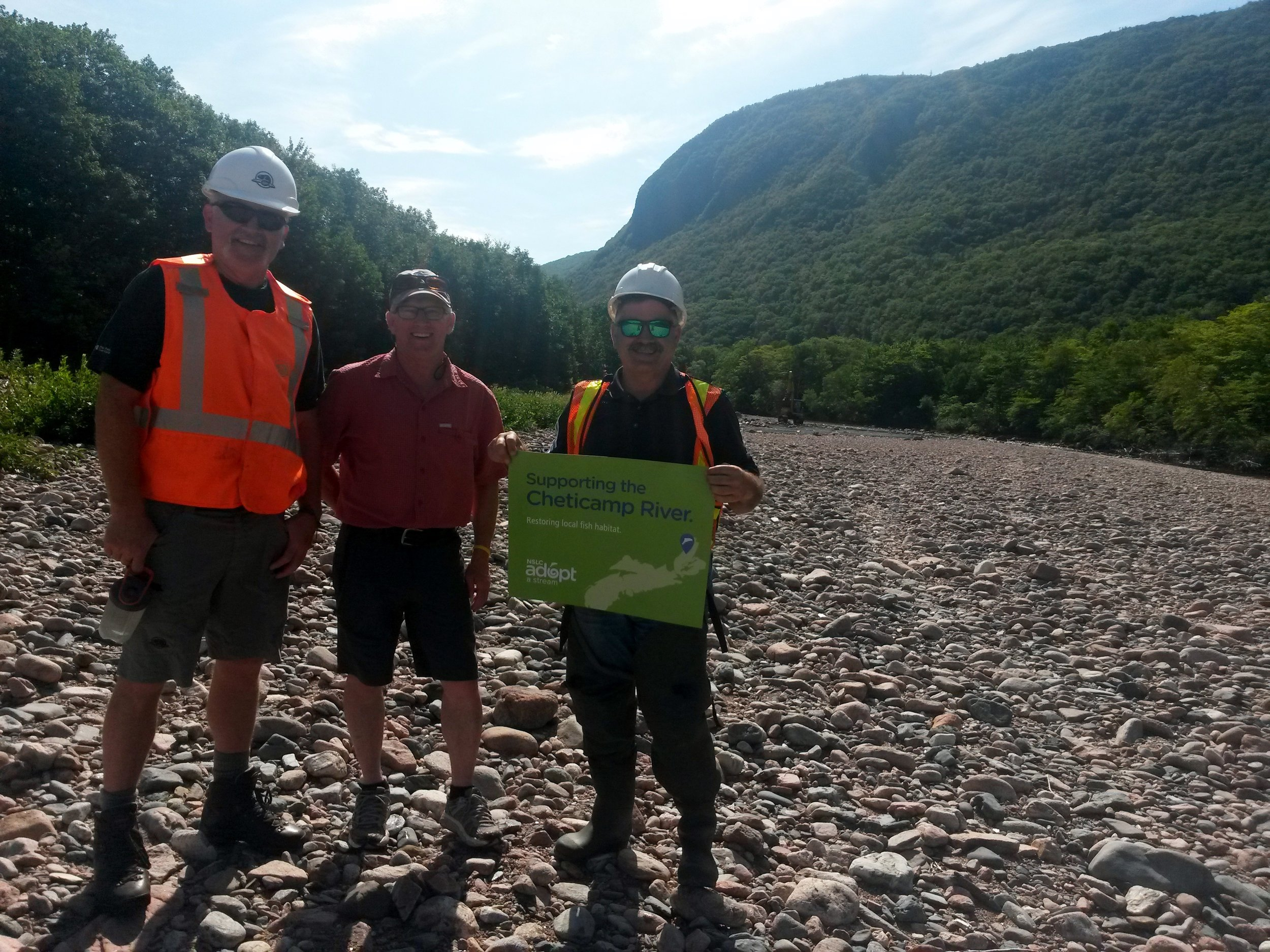Archie Doucette (Parks Canada), Rene Aucoin (CRSA President), and Charles MacInnis (Project consultant) (left to right) pose with signage from the Nova Scotia Salmon Association's NSLC Adopt-a-Stream Program, one of the funders of the Cheticamp River restoration project.