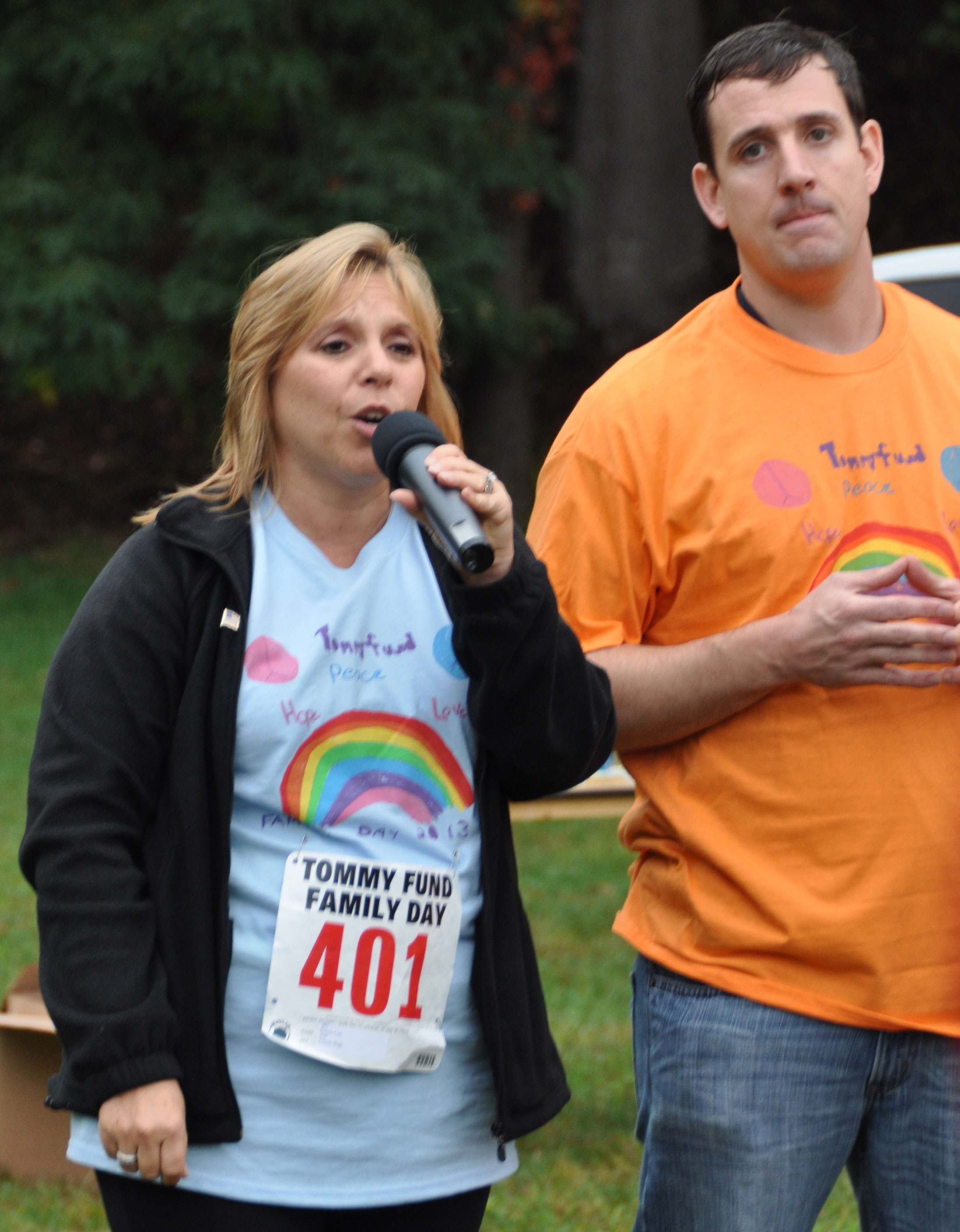 Oncology nurse Denise Carr sings the national anthem while Joe Bowman looks on.