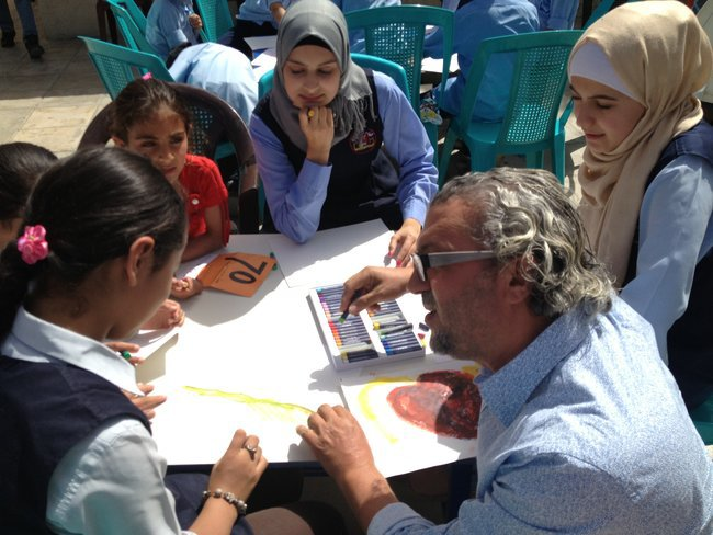 The artist Suheil Baqaeen helped a student with a drawing while classmates looked on.