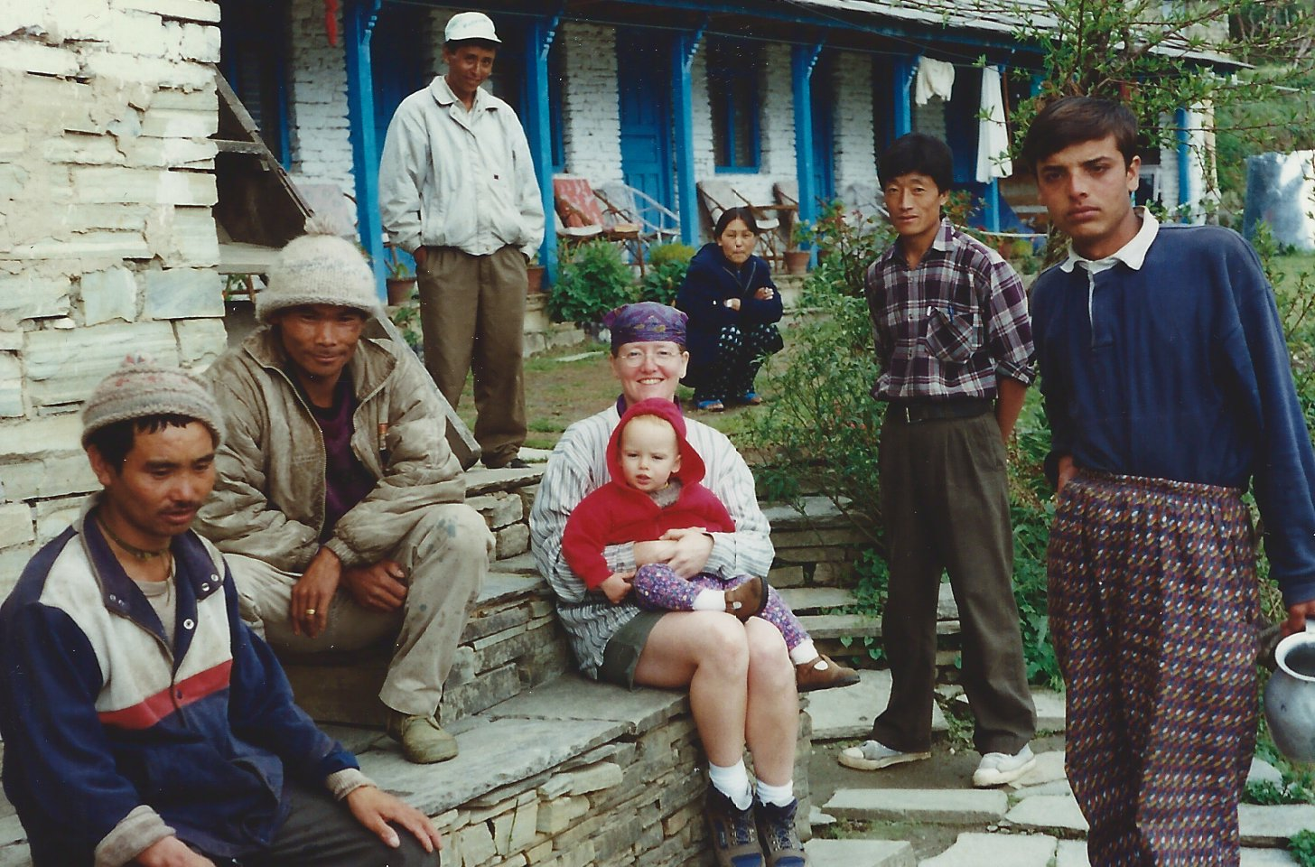 """That's me and baby Lily (17 months) in Nepal with our Nepalese """"family."""" My knee was working fine at this point. My trusty walking stick. It would come to me later in our journey, when we still had not reached our destination and my strength of will was beginning to falter as a result of the pain. These friends and that stick would eventually help get me to the top of the Annapurna Sanctuary. It was worth every ounce of strain and effort."""