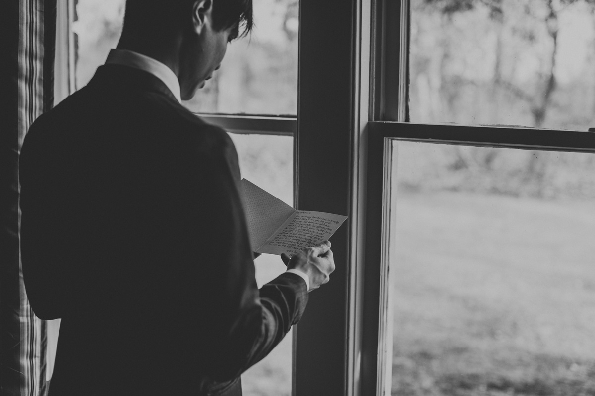groom-reading-note-from-bride-wedding-photography