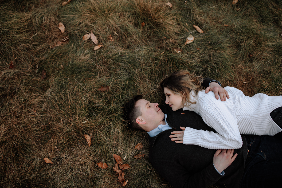 couple-laying-on-grass-engagement-photos