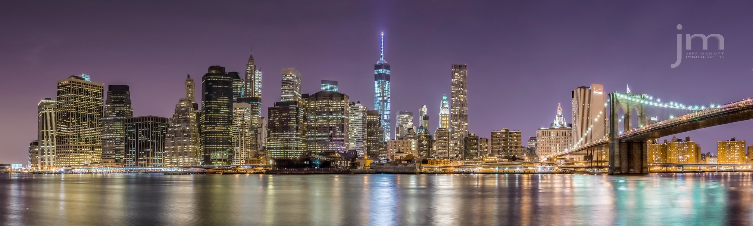 Panoramic shot of Manhattan and the Brooklyn Bridge from Brooklyn. Freedom Tower is standing in the center of this picture.