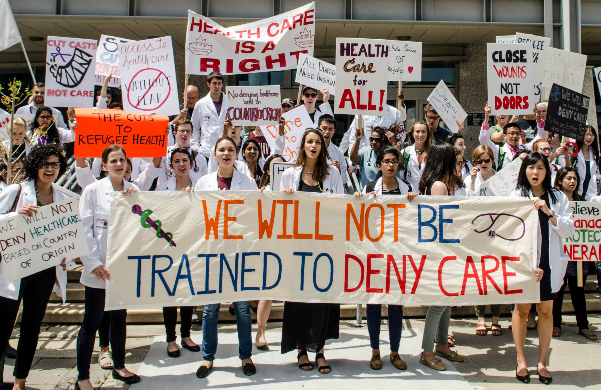 "Nicole with fellow McMaster medical students, and Hamilton physicians, nurses, allied health staff, family and friends uniting on June 15th, 2015 for the National Day of Action for Refugee Health.  ""We openly denounced the federal government's cuts to the Interim Federal Health Program's coverage of refugee healthcare. We will not be taught to deny care. More info at  http://www.doctorsforrefugeecare.ca/day-of-action-june-15-2015.html ."""