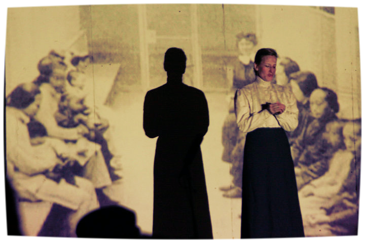 Andrea Day as the missionary, Miss Gregory, in front of archival image of detained Chinese women on Angel Island.