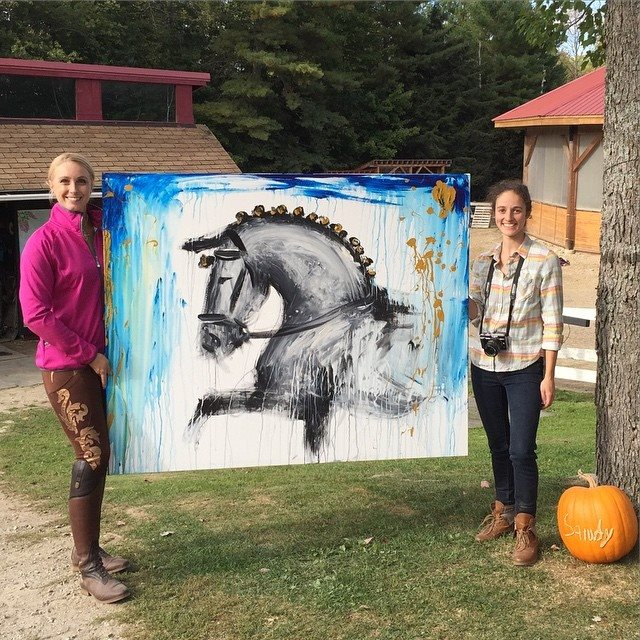 Sandra beaulieu and taylor burdin hold the finished painting before it is signed.
