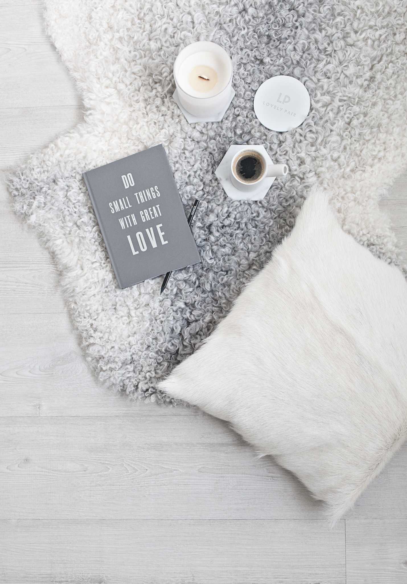 Lovely Pair  White VOGUE Candle |   Milabert   Gotland Sheepskin Rug & Cushion |   Serax   white Catherine Lovatt ceramic cup | Notebook from The White Company