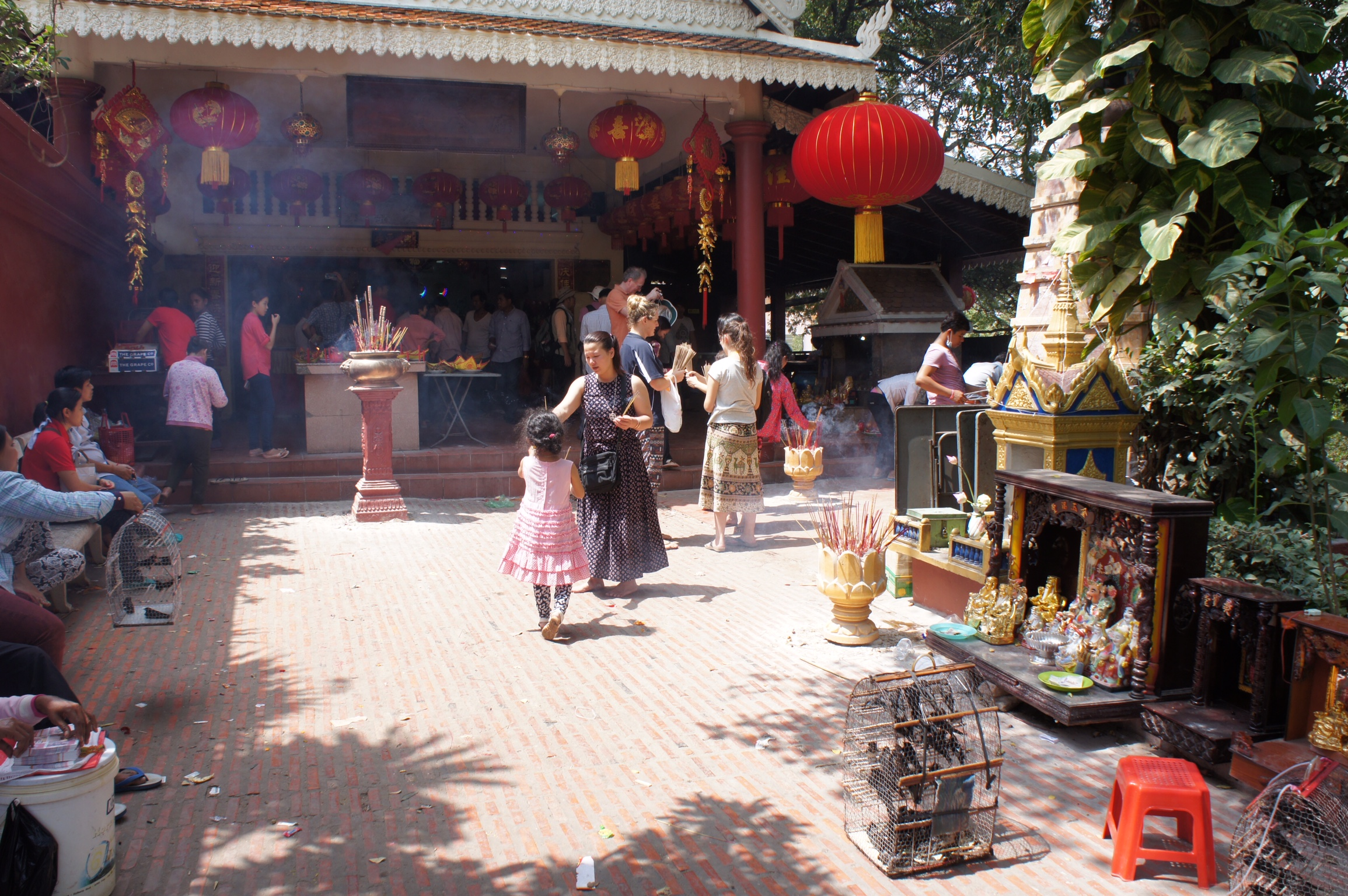 Celebrations for the Lunar New Year at Wat Phnom. To the right, is the furnace for burning replicamoney and forefront is a cage of birds, one of which you can hold and release for a fee. The birds typically return after they've been set free and are sold again.