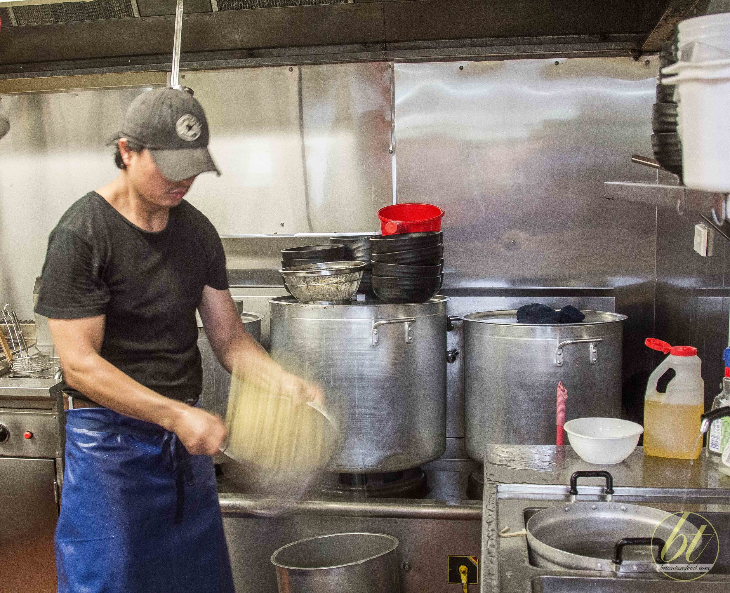 Chef O-San draining the cooked noodles of any excess water by giving the colander a few big shakes!