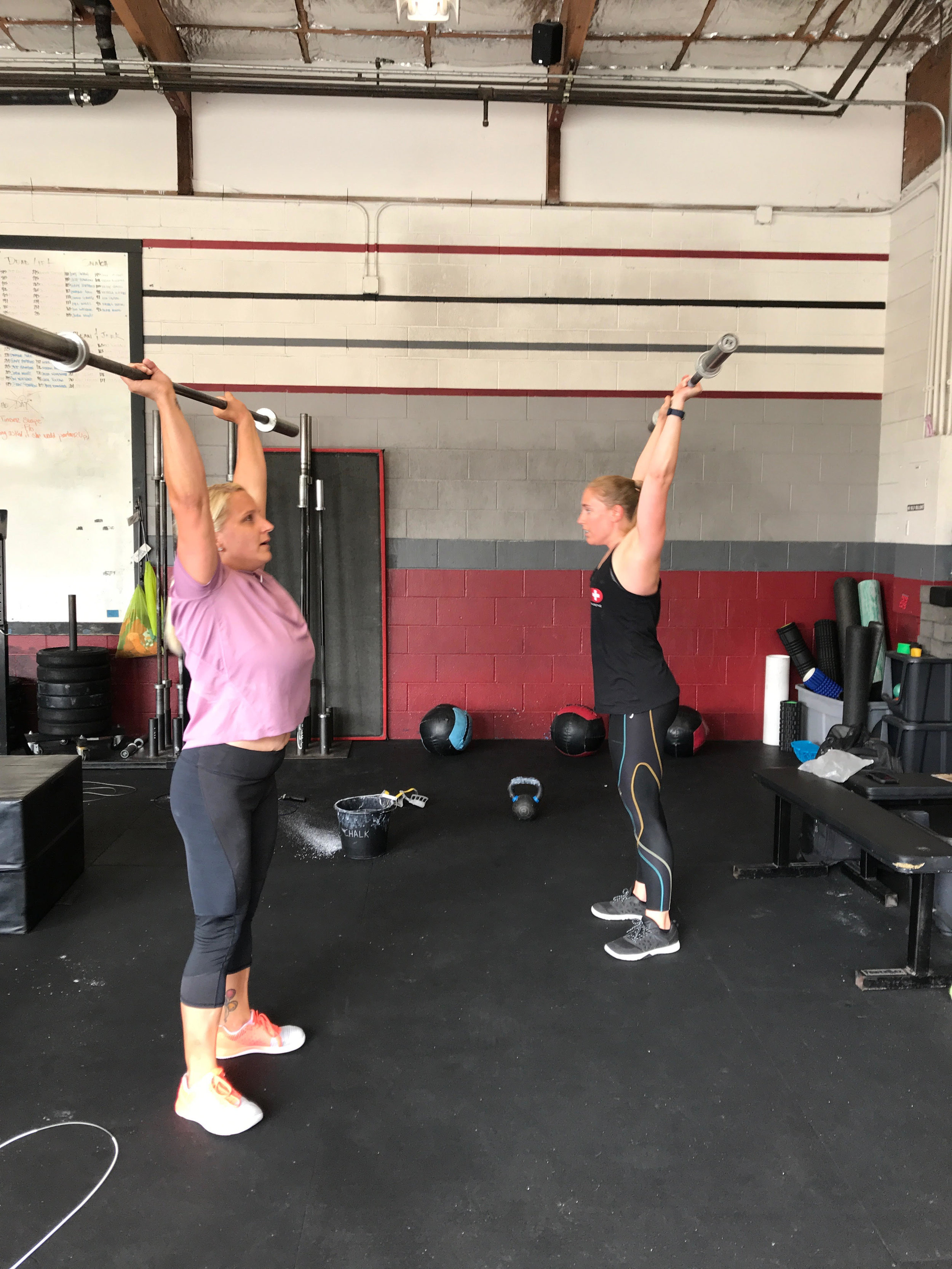 Janea and Kate with the barbell overhead.