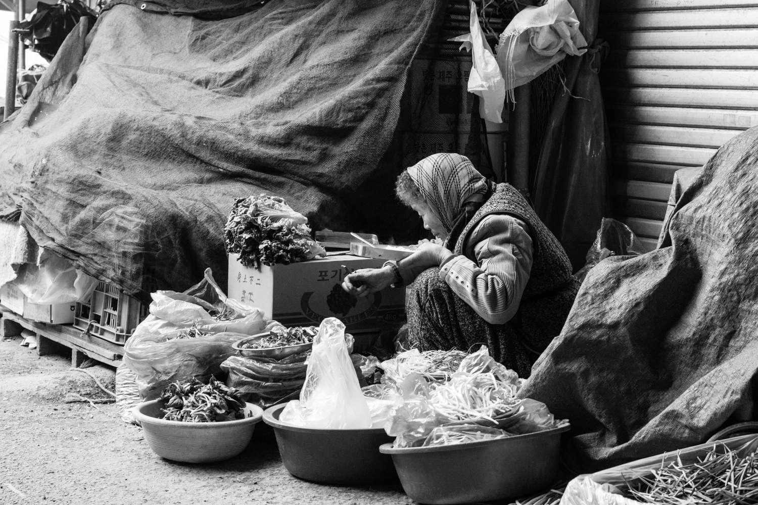 A lunch break for one of the poorer merchants at Yang-dong market. Vendors like this one likely grow their own produce in whatever meagre plots of land are available around their house. The produce is often wilted, and there is never much on offer.