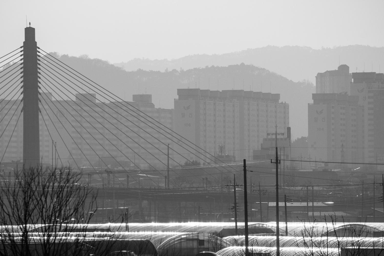 Greenhouses, a bridge, and apartments in Gwangju.
