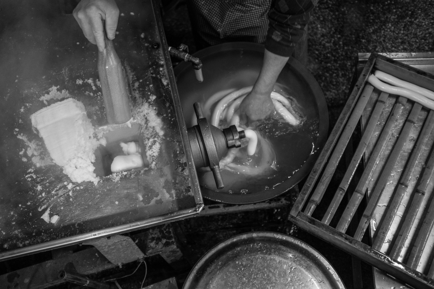 Forcing a block of steamed rice flour through the extruder into water.