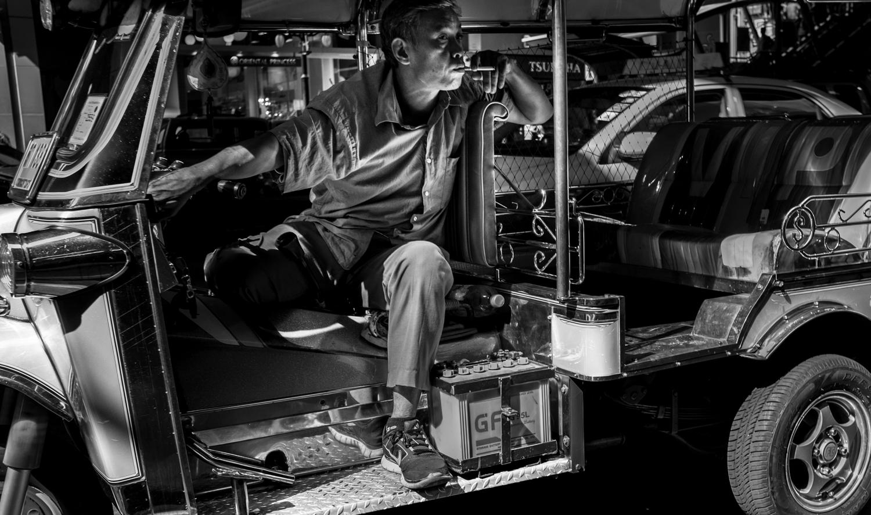 A tuk tuk driver waits for a fare.
