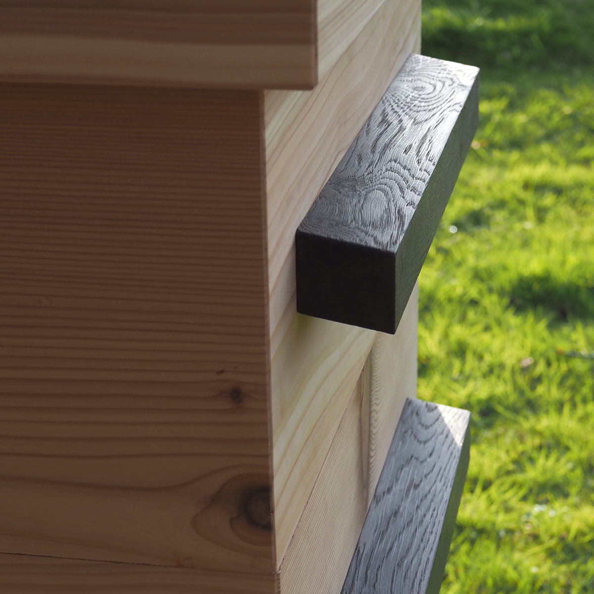 close-up-of-charred-oak-handles-on-beehive.jpg