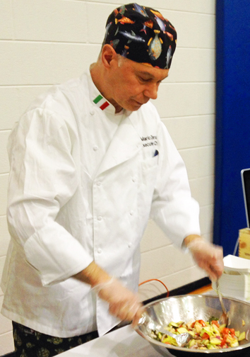 Chef Mario prepares Panzanella salad for eager taste testers at the Leelanau Peninsula Chamber of Commerce 2014 business expo.