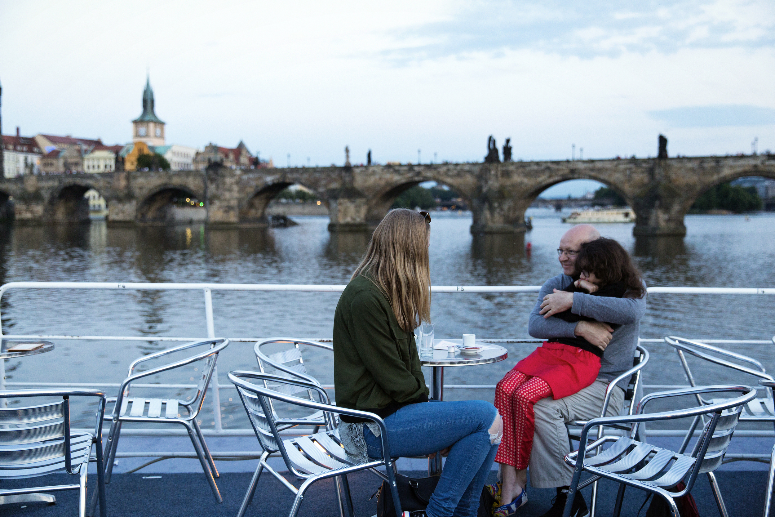 A European family enjoys a ride down the Vltava River one evening.