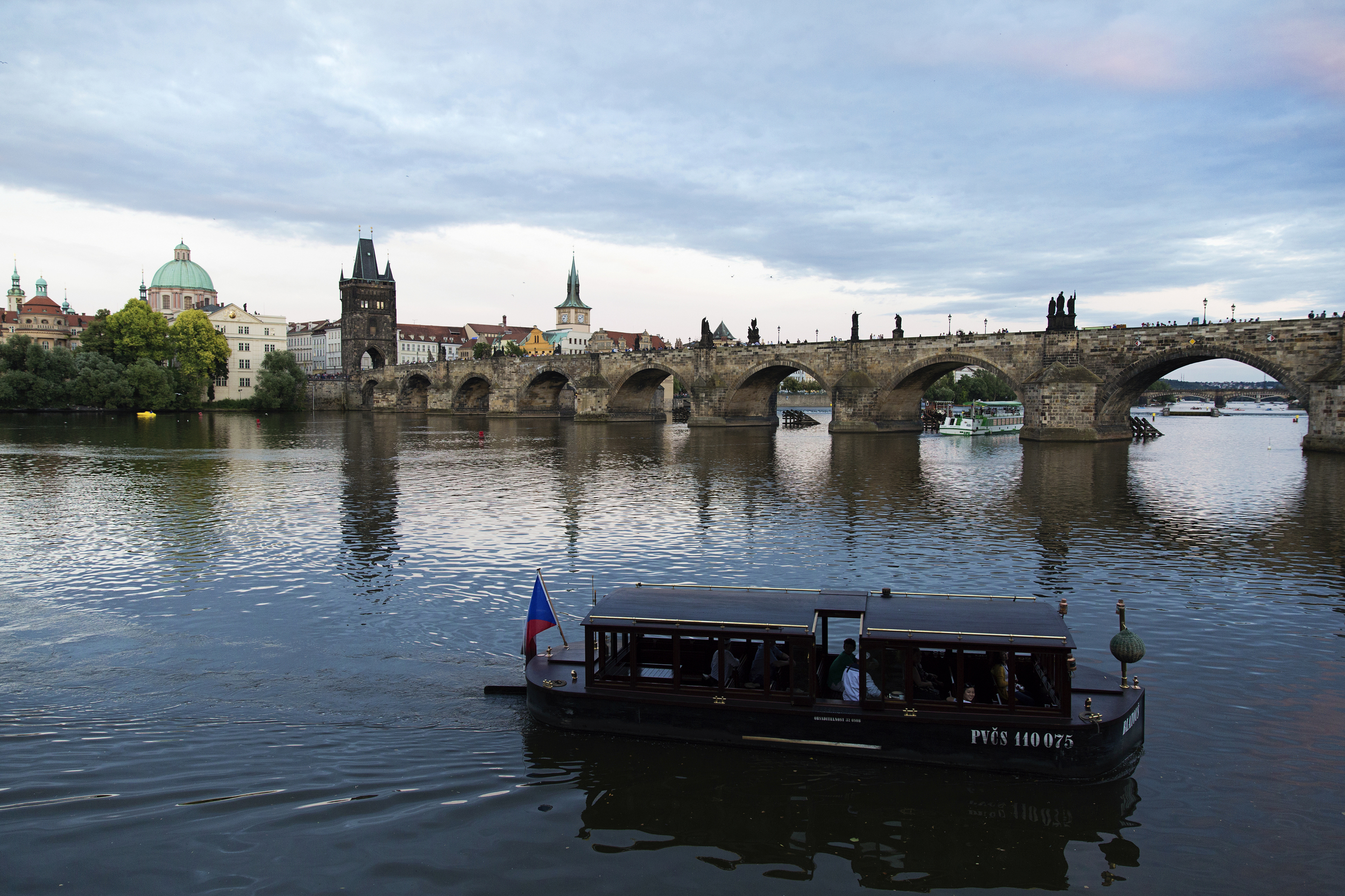A boat floats along the Vltava River near the Charles Bridge.