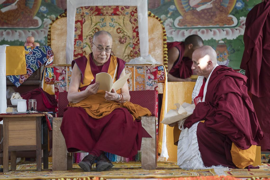 His Holiness examines the new Rato Chayik Chenmo—Great Constitution of Rato Monastery—which he composed.  Photo by Tenzin Choejor—OHHDL