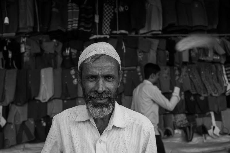 the shopkeeper from Mundgod happy to say Tashi Delek as his assistant dusts the merchandise