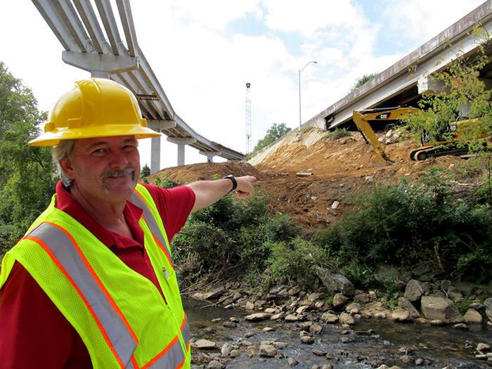 Georgia Department of Transportation employee points to the site of the future bridge.