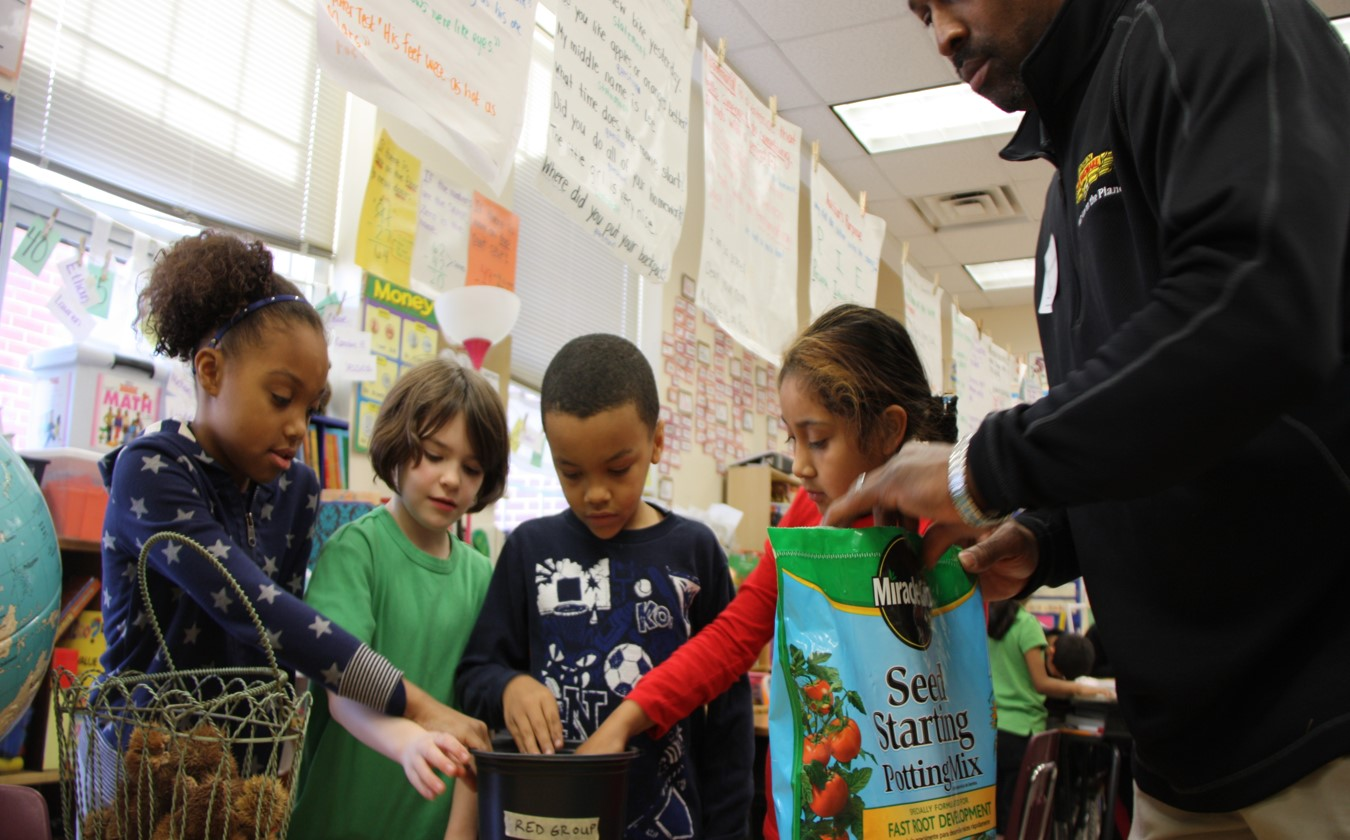 SFC Board Member Tony Powers helps 2nd graders at Garden Hills Elementary plant their seeds in the fall of 2013.