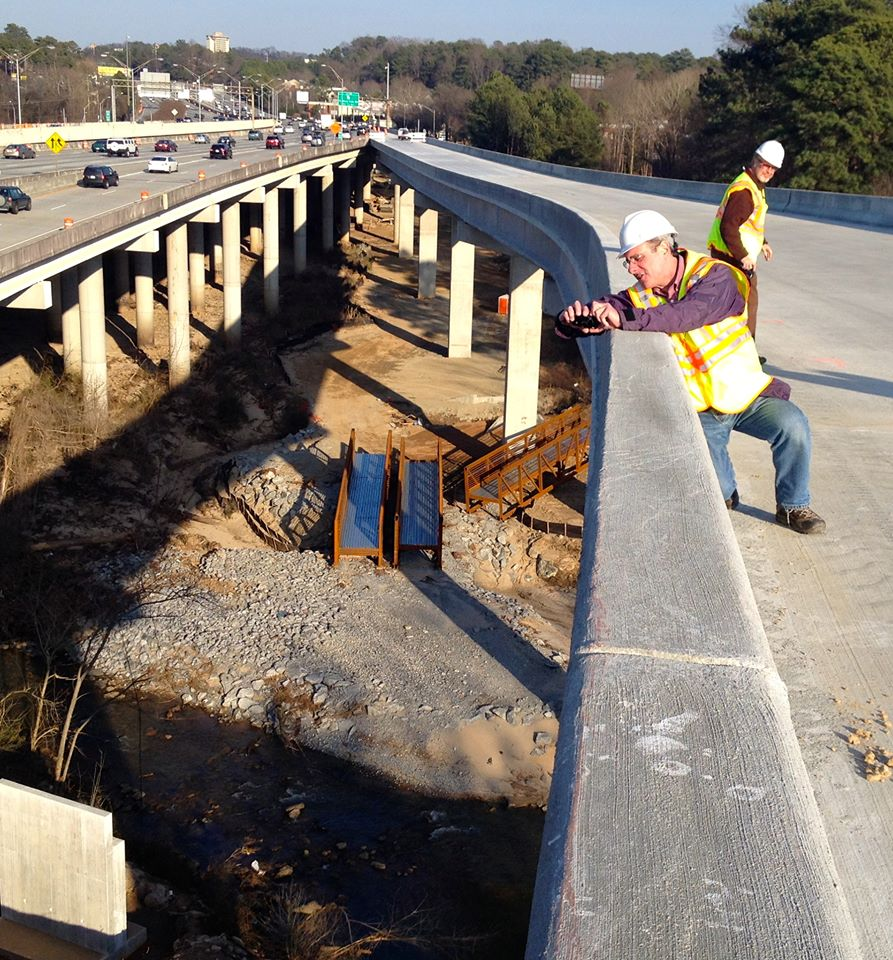 This was the last rush hour where cars moved easily for the rest of the week. Snow & ice locked it away. Looking East toward the Druid Hills Exit. Note the rust-colored footbridge on the ground in pieces. One week later, Archer Western crews used two cranes to lift the pieces onto concrete footings well above the flood levels.