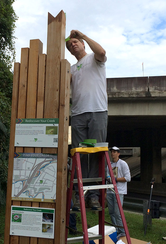 SFC board member Warner McConaughey installs signs at Lindbergh and Meadow Trail.