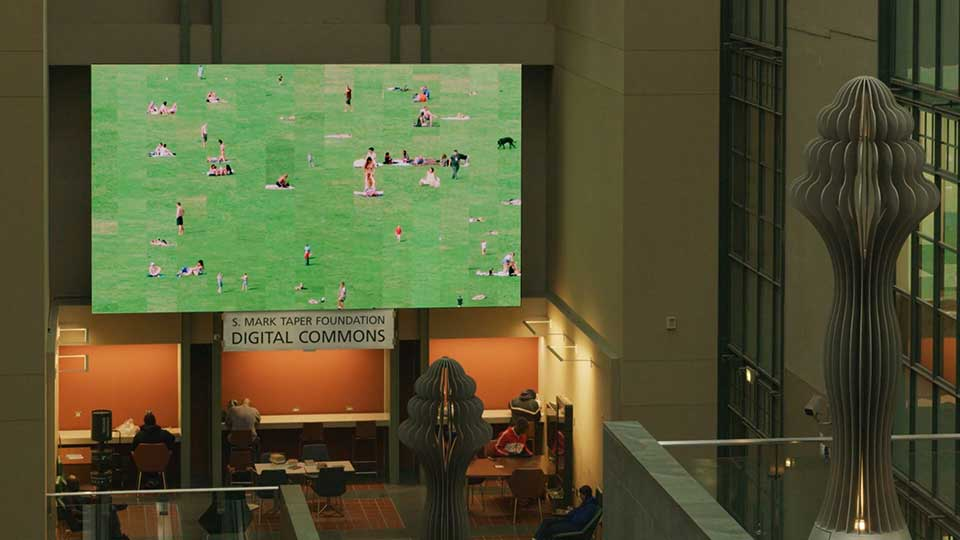 """Installation view of """"Green Play"""" on the 28 foot video wall in Los Angeles Public Library"""