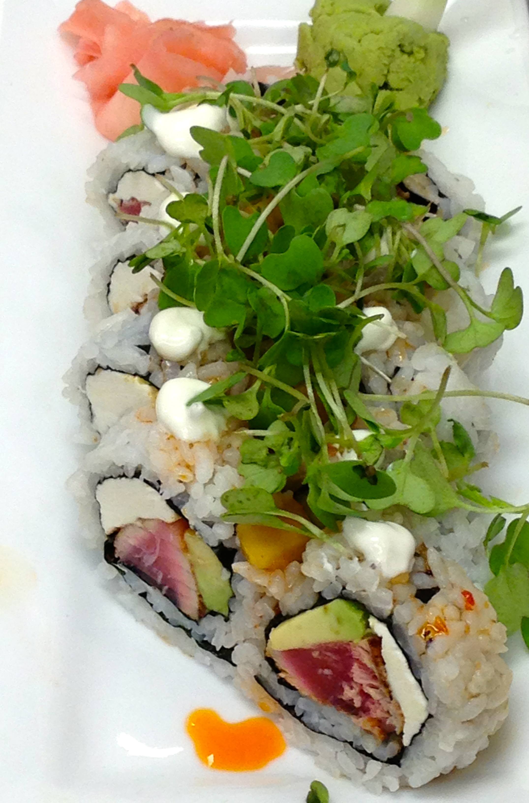 Blackened Tuna Roll with hot sesame oil, lime creme fraiche, mango salsa, and wasabi greens