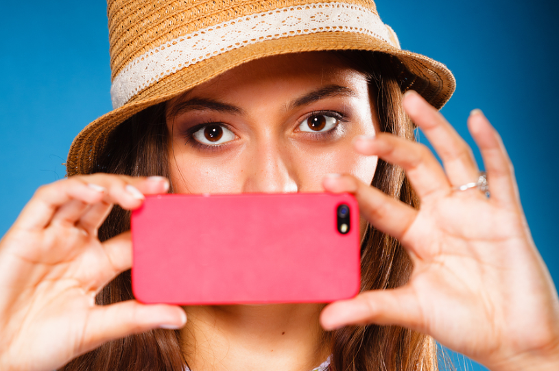 Stock photo of woman with pink smartphone.
