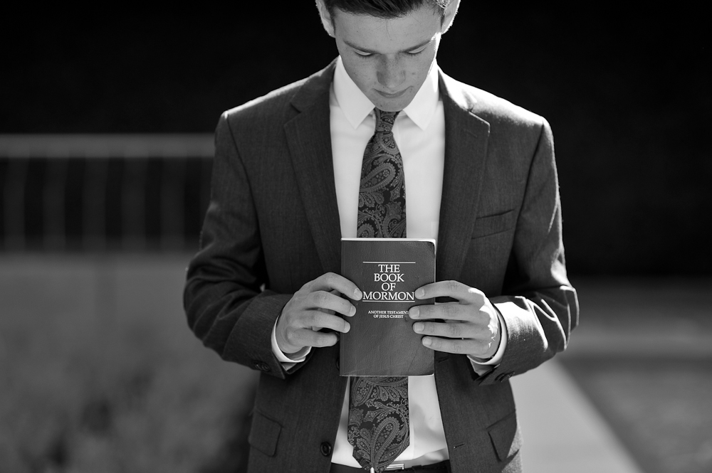 LDS Missionary holding a Book of Mormon