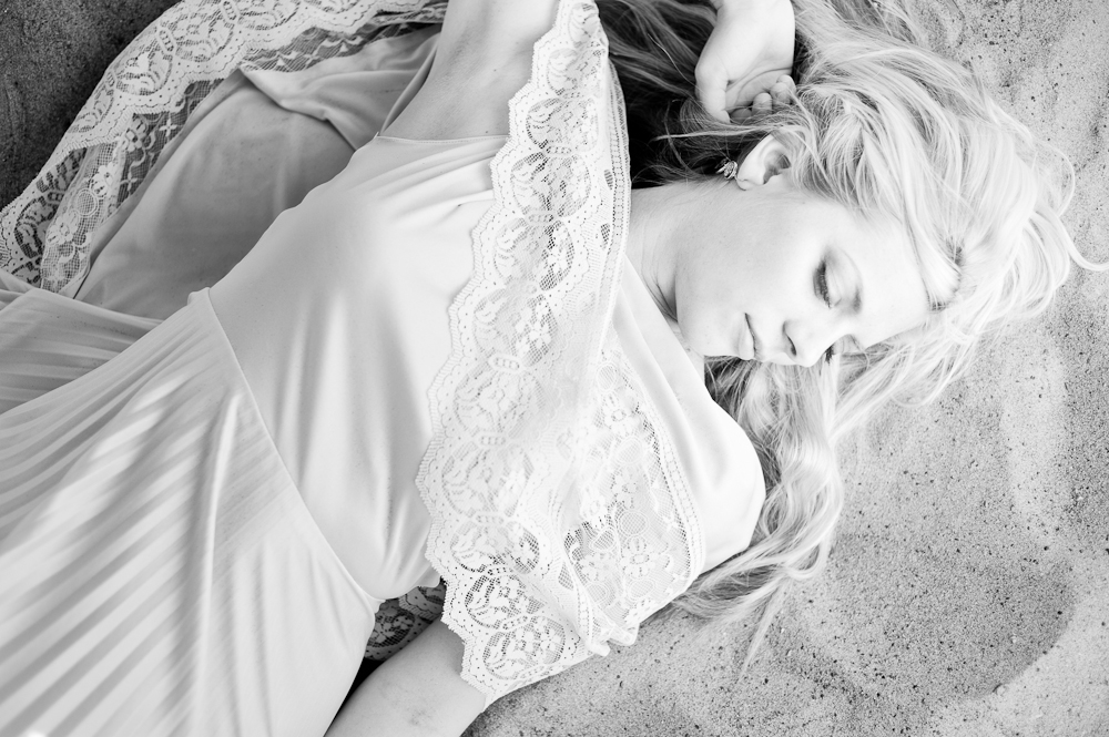 black and white girl laying in the sand