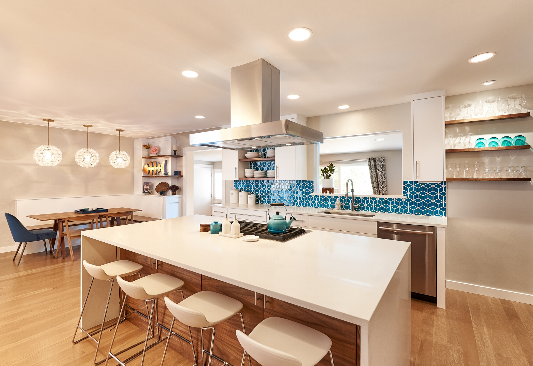 Open kitchen with white quartz counter and modern bar stools and built in. stove in island and 328 interior design group - chance lanphear photography
