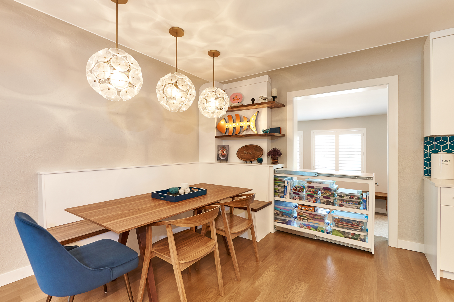 custom built-in with bench seating and oversize storage walnut and display shelves white pendant lights in kitchen