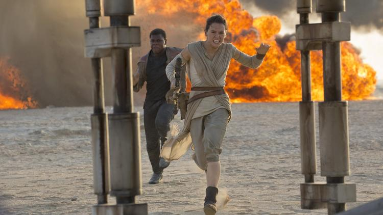 "Rey (Daisy Ridley) and Finn (John Boyega) run for their lives in ""Star Wars: The Force Awakens."" (David James / Disney / Lucasfilm)"